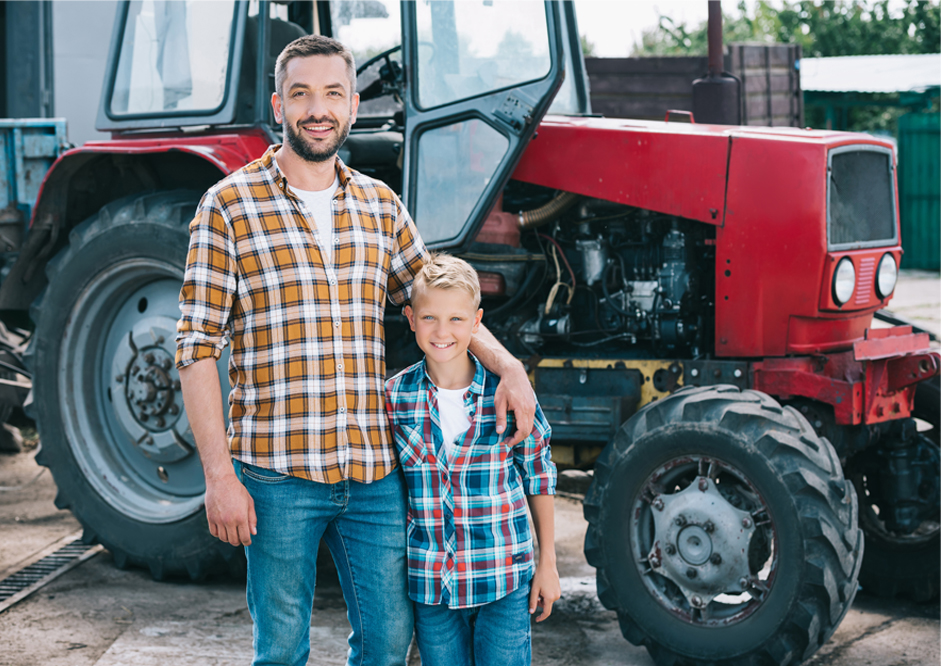 father and son standing near tractor